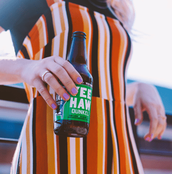 Woman in striped dress holding a bottle of Yee-Haw Dunkel beer.