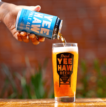 A can of Yee-Haw Pale Ale is poured into a Yee-Haw glass.